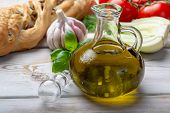 Virgin Natural Olive Oil Is Glass Bottle, Served With Traditional Mediterranean Food poster