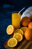 A Glass Of Fresh Orange Juice With A Tube, Orange Slices, Oranges, White Cloth On A Dark Blue Backgr poster
