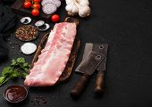 Fresh Raw Pork Ribs On Chopping Board And Vintage Meat Hatchets On Black Stone Background. Fresh Tom poster