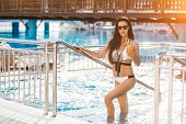Pretty Young Slim Woman With Long Dark Hair Standing In The Swimming Pool With Cocktail Wearing In W poster
