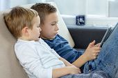 Two Kids Using Touchscreen Tablet At Home, Modern Education Technology. Brothers With Tablet Compute poster