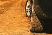 Close Up Of Car Tires On Dirt Country Road In Summer Afternoon poster