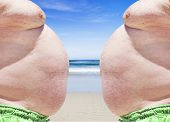 stock photo of fat-guts  - Close up of obese twins on the beach showing their unhealthy bellies - JPG