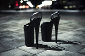 Womens High-heeled Shoes. Shoes For Strip Standing On The Cobblestones At Night In The City. Extreme poster