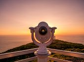 Image Of Viewpoint With Binoculars During Colorful Sunset Pointing At The Ocean poster
