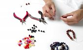 Making Bracelet Of Colorful Beads. Female Hands With A Tool On A White Background. Selective Focus. poster