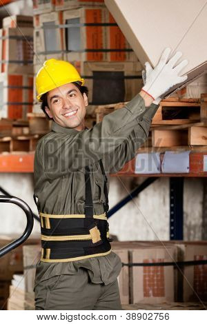 Happy foreman lifting a cardboard box at warehouse