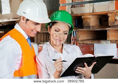 Young female supervisor and colleague working at warehouse