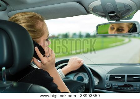 Young woman with telephone having phone conversation while driving car