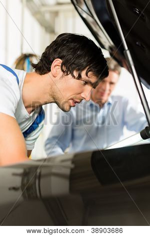 Mature man - client - and young mechanic are looking beneath a hood with a lamp