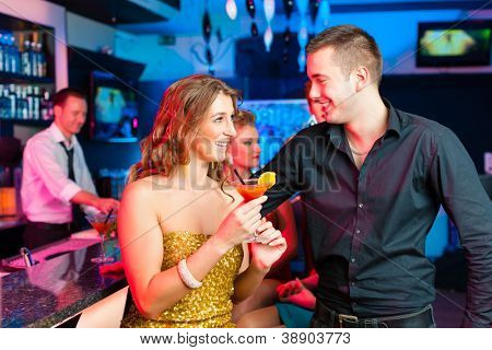 young couple in bar or club drinking cocktails, it might be the first date