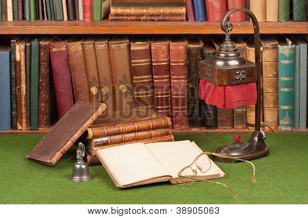 Antique leather books lamp and reading glasses on green blotter.