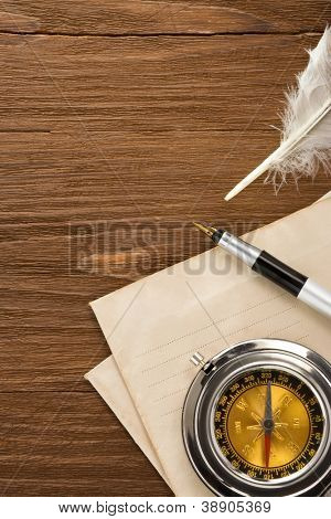 compass and ink pen at envelope on vintage wood background texture