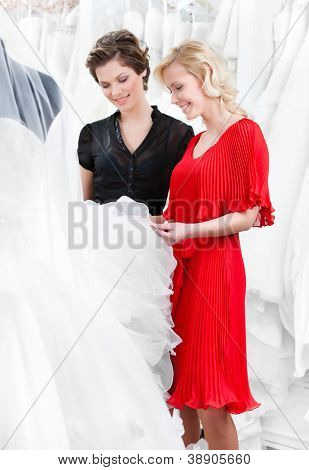 Girl hesitates about wedding gown. Shop assistant advises the client to select a proper dress