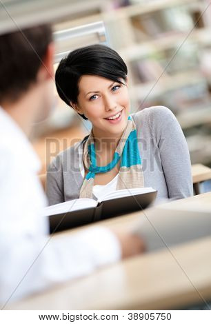 Pretty woman communicates with handsome man showing her something in the book sitting at the desk at the library
