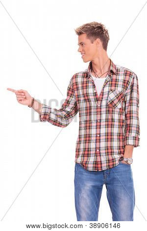 young casual man pointing and looking to his side and holding a hand in his pocket, on white background