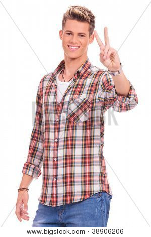 portrait of a casual man showing victory sign and smiling to the camera on white background
