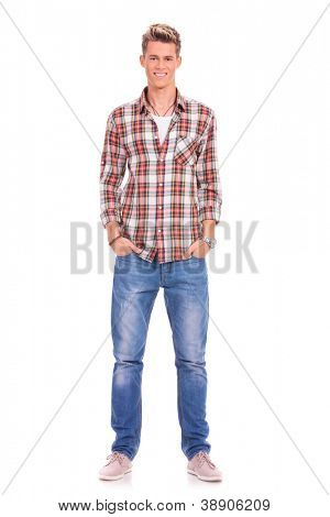 Full length portrait of happy handsome casual young man standing with his hands in his pockets isolated on white background