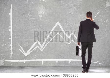 back view of a business man holding a briefcase and talking on his smartphone while looking at a growing graph