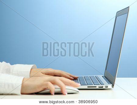 female hands writing on laptot, on blue background
