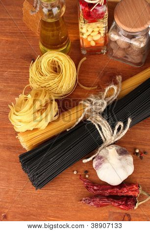 Pasta spaghetti, vegetables and spices on wooden table on wooden background