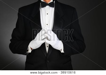 Closeup of a man wearing a tuxedo with his hands together in front of his torso. Man is unrecognizable. Horizontal format on a light to dark gray background.