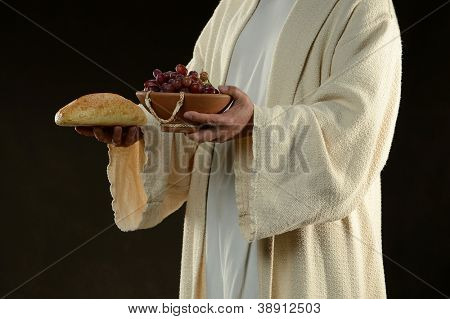 Jesus holding a bread and grapes as a metaphor