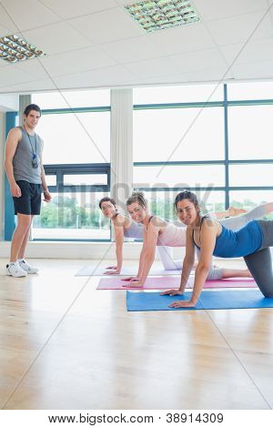 Yoga class with male instructor smiling in fitness studio