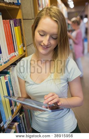 Woman standing at a bookshelf holding a tablet pc in college library
