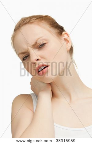Young woman massaging her painful back against white background