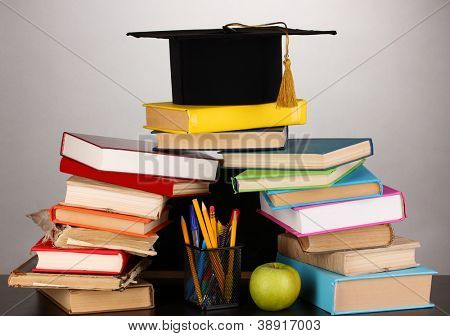 Books and magister cap against school board on wooden table on grey background