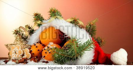 christmas composition with oranges and fir tree in Santa Claus hat