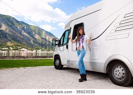 Portrait of a happy young woman standing in front of motor home