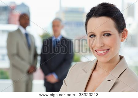 Young secretary standing upright in a relaxed way and showing a beaming smile
