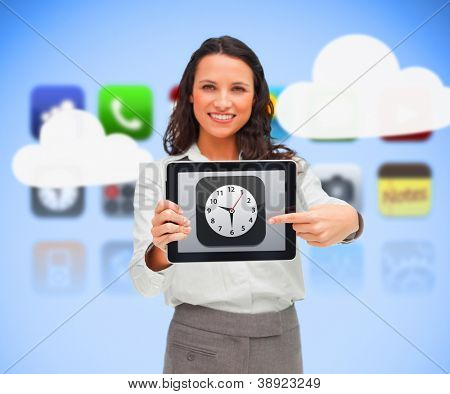 Businesswoman standing while holding a tablet pc pointing to clock app symbol on background of phone applications and clouds