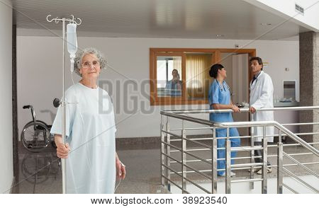 Old woman standing in the hallway in a hospital holding a drip