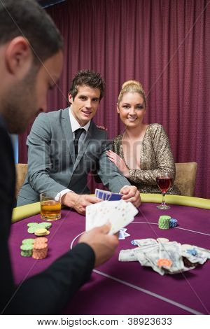 Happy couple playing poker in casino