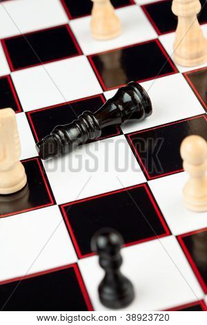 Black queen lying at the chessboard while white chessmen standing