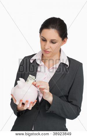 Brunette in suit putting dollars into a piggy-bank against white background