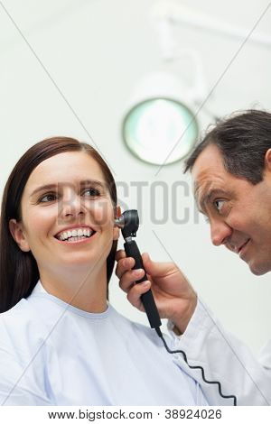 Doctor using an otoscope to look at the ear of a patient in an examination room