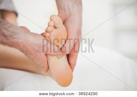 Physiotherapist using his fingers to massage a foot in a room
