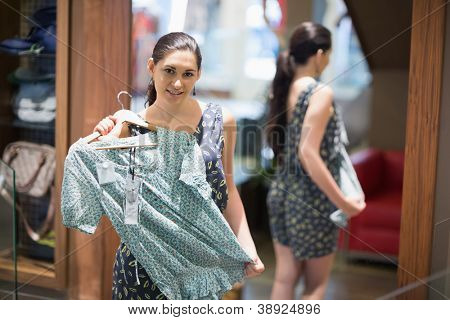 Woman holding up shirt in clothes store