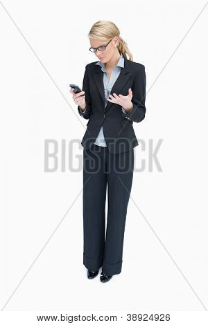Business woman standing and looking angrily at mobile phone
