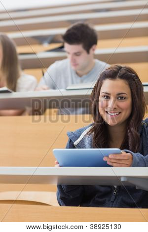 Woman holding a tablet pc while smiling and looking up in lecture hall