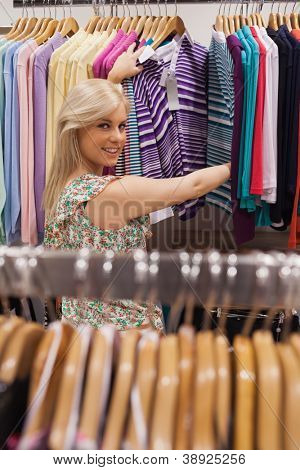 Woman standing by the clothes rack of a boutique smiling