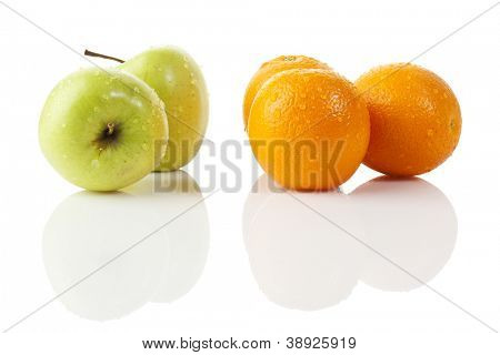two green apples and three oranges with water drops isolated on white background