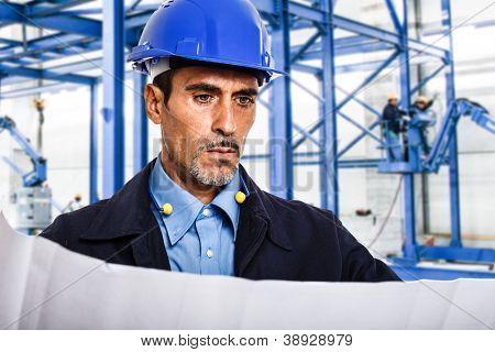 Portrait of an engineer reading a blueprint