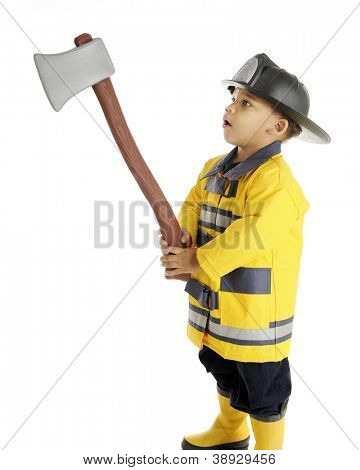 An adorable preschool fireman examining his raised hatchet.  On a white background.