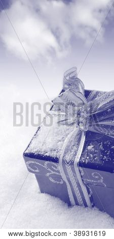 Christmas time - duotone box in snow on blue sky