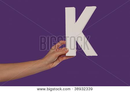 Female hand holding up the uppercase capital letter K isolated against a purple background conceptual of the alphabet, writing, literature and typeface